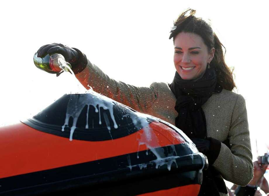 Kate Middleton, the fiance of Britain's Prince William, pours champagne over the 'Hereford Endeavour', during a naming ceremony and Service dedication for the Royal National Lifeboat Institution's new Atlantic 85 Lifeboat, at Trearddur Bay Lifeboat Station in Anglesey,  Wales, Thursday Feb. 24, 2011. The visit had been highly anticipated because the couple have kept such a low profile since announcing their engagement in November, making only one other prior appearance at a charity event. They plan to marry April 29 at Westminster Abbey with just under 2,000 guests attending. (AP Photo/Phil Noble, Pool) Photo: PHIL NOBLE / POOL REUTERS