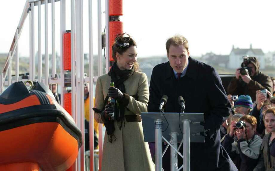 Britain's Prince William, right, looks on as his fiancee Kate Middleton prepares to pour champagne over the lifeboat during a visit Trearddur Bay Lifeboat Station on the island of Anglesey, Wales, Thursday, Feb. 24, 2011. Several hundred people cheered as Prince William and fiancee Kate Middleton made a rare public appearance Thursday to dedicate a new lifeboat. They plan to marry April 29 at Westminster Abbey. (AP Photo/Jon Super) Photo: JON SUPER / AP