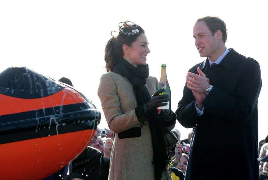 Britain's Prince William applauds after his fiance Kate Middleton poured champagne over the 'Hereford Endeavour' a new RNLI lifeboat, during a Naming ceremony and Service dedication, at Trearddur Bay Lifeboat Station in Anglesey,  Wales, Thursday Feb. 24, 2011. The visit had been highly anticipated because the couple have kept such a low profile since announcing their engagement in November, making only one other prior appearance at a charity event. They plan to marry April 29 at Westminster Abbey with just under 2,000 guests attending. (AP Photo/Phil Noble, Pool) Photo: PHIL NOBLE / POOL REUTERS
