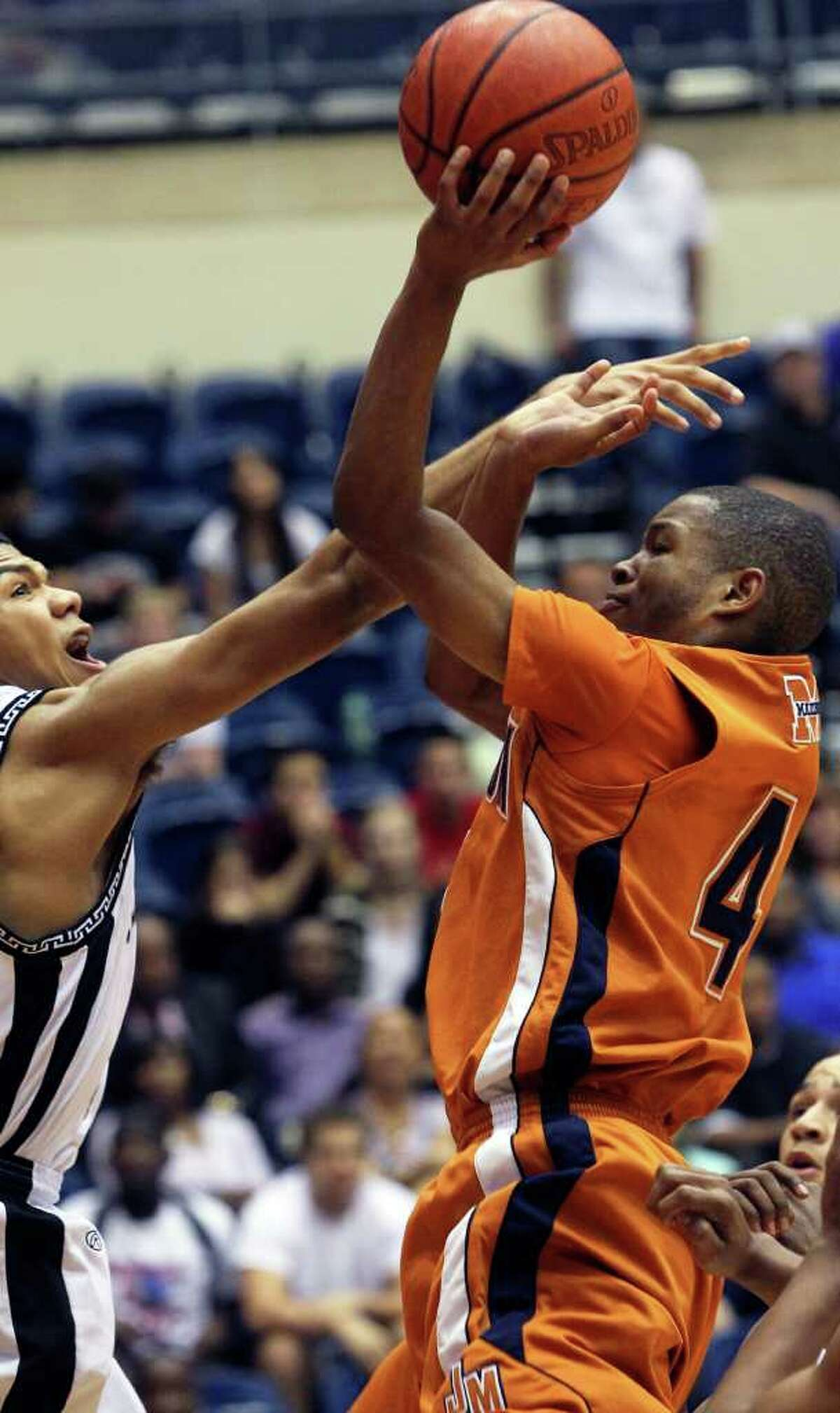 SPORTS Madison guard Byron Daniels shoots through tough defense by Niko Maxwell as Clark beats Madison 49-37 in 5A boys basketball playoffs at the UTSA Convocation Center on February 24, 2011. Tom Reel/Staff