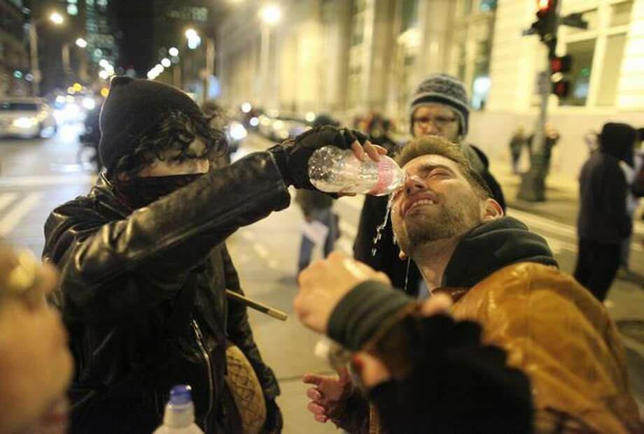 Protester Mike Stevens has his eyes cleaned after he was hit with pepper spray during Friday night's protest. Photo: Joshua Trujillo/seattlepi.com