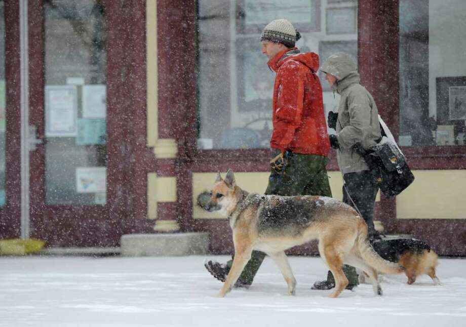 Bruce Cranston and Lisa Nagle take their dogs for a walk on Broadway in Saratoga Springs, New York February 25, 2011 as the region is hit with another forecast heavy snowfall.  (Skip Dickstein / Times Union) Photo: SKIP DICKSTEIN / 2008