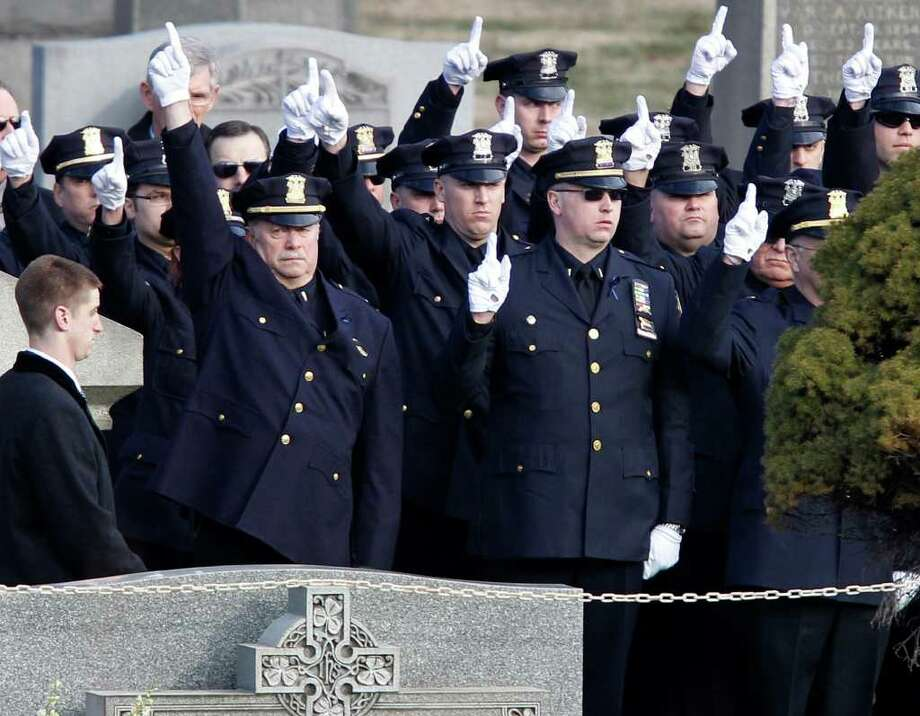 Police officers hold their gloved fingers in the air at the burial of slain Poughkeepsie police Detective John Falcone at Brooklyn's Holy Cross Cemetery in New York, Thursday, Feb. 24, 2011.  Falcone was killed as he helped rescue a 3-year-old girl. (AP Photo/Kathy Willens) Photo: Kathy Willens
