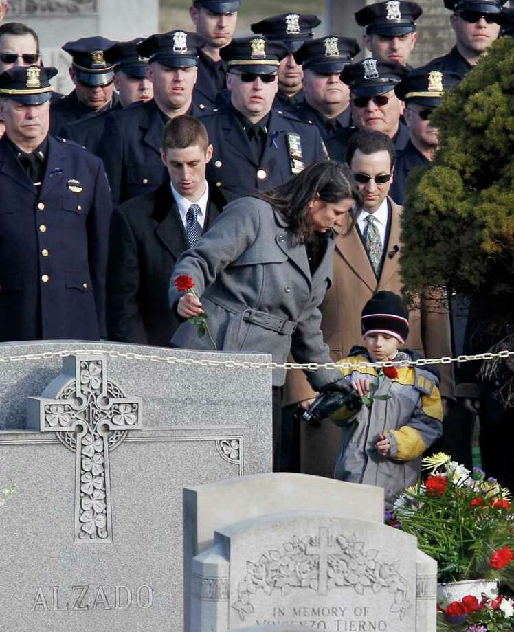 Relatives of slain Poughkeepsie police Detective John Falcone, 44, lay carnations at his gravesite during burial for the 14-year police veteran at Brooklyn's Holy Cross Cemetery in New York, Thursday, Feb. 24, 2011.  Falcone was killed as he helped rescue a 3-year-old girl. (AP Photo/Kathy Willens) Photo: Kathy Willens
