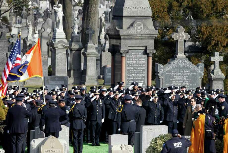 Officers salute during the burial for slain Poughkeepsie police Detective John Falcone, a 14-year veteran of the department, at Brooklyn's Holy Cross Cemetery in New York, Thursday, Feb. 24, 2011.  Falcone was gunned down as he helped rescue a 3-year-old girl. (AP Photo/Kathy Willens) Photo: Kathy Willens