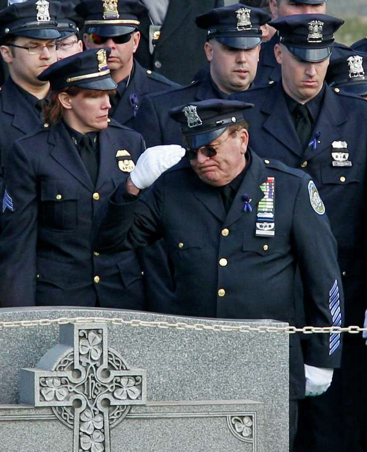 A fellow officer gives a farewell salute to his slain colleague at the gravesite of Poughkeepsie police Detective John Falcone at Brooklyn's Holy Cross Cemetery in New York, Thursday, Feb. 24, 2011. Falcone was gunned down as he helped rescue a 3-year-old girl. (AP Photo/Kathy Willens)