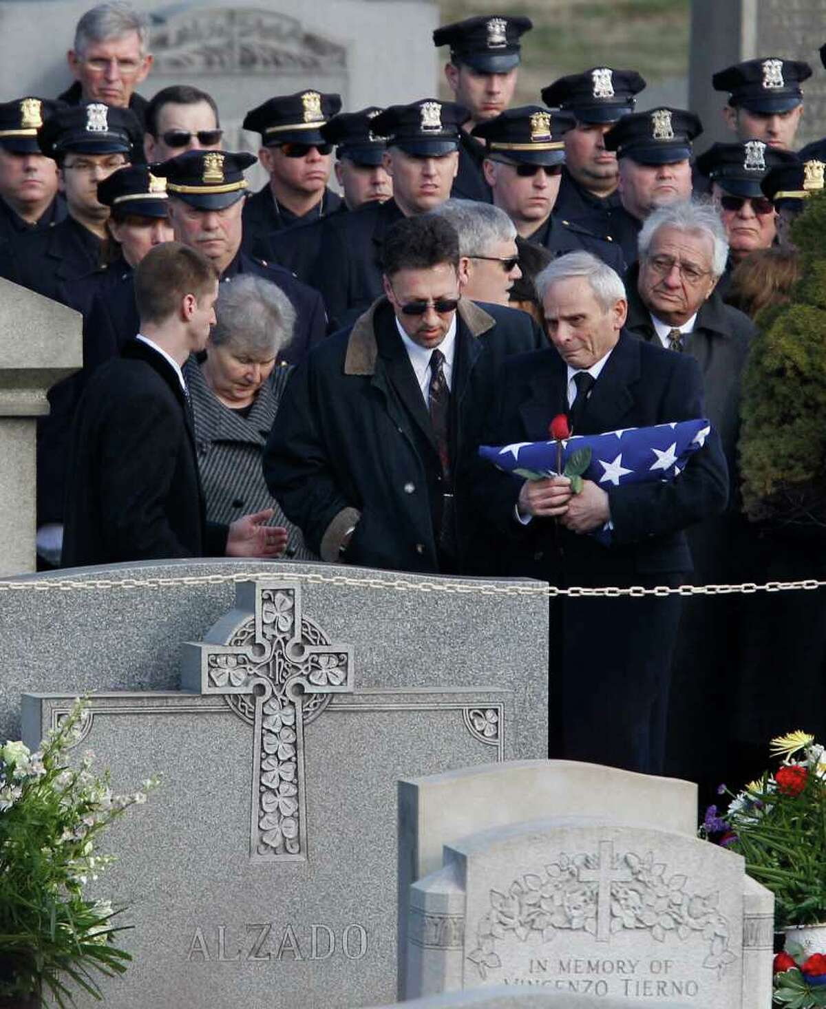 Police officers look on as a family member is brought toward the gravesite at the burial of slain Poughkeepsie police Detective John Falcone at Brooklyn's Holy Cross Cemetery in New York, Thursday, Feb. 24, 2011. Falcone was gunned down as he helped rescue a 3-year-old girl. (AP Photo/Kathy Willens)