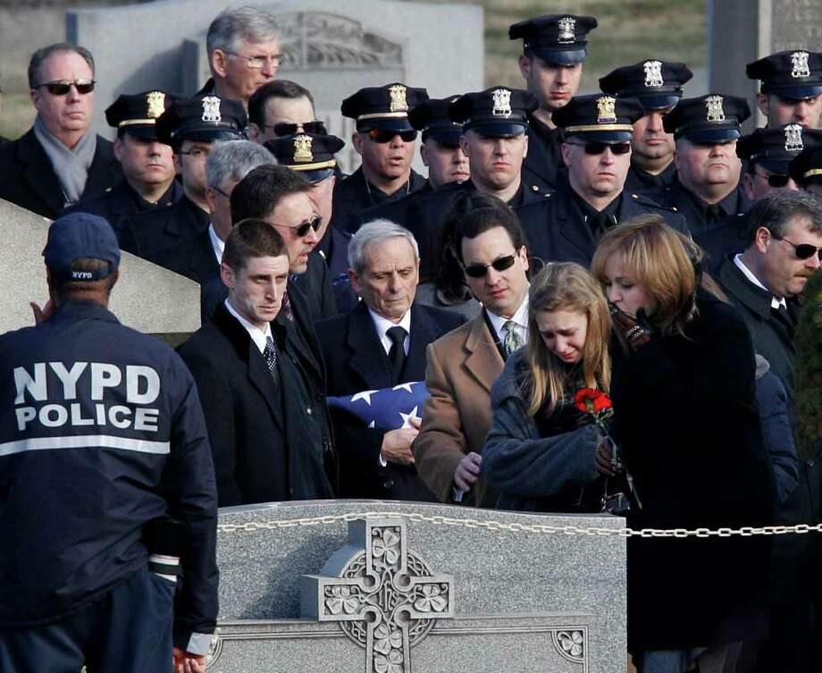 Family members pay their respects at the burial of slain Poughkeepsie police Detective John Falcone at Brooklyn's Holy Cross Cemetery in New York, Thursday, Feb. 24, 2011. Falcone was killed as he helped rescue a 3-year-old girl. (AP Photo/Kathy Willens) Photo: Kathy Willens