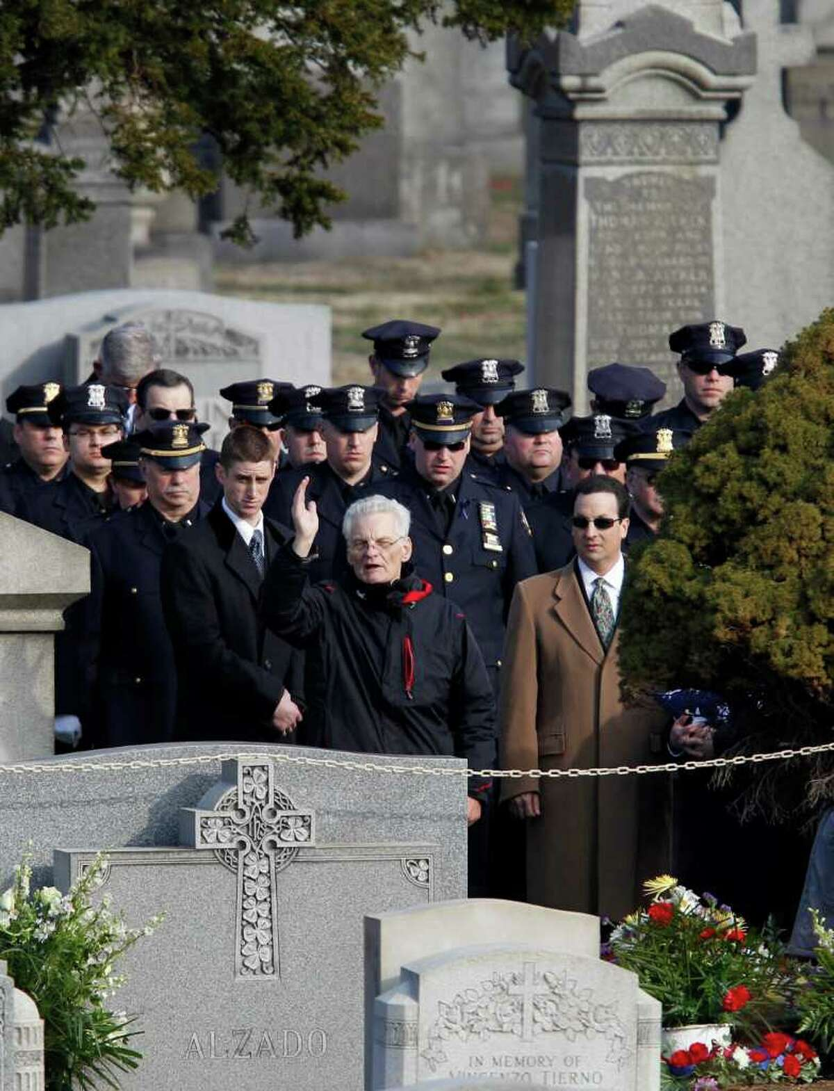 Police officers look on as a priest presides over the burial of slain Poughkeepsie police Detective John Falcone at Brooklyn's Holy Cross Cemetery in New York, Thursday, Feb. 24, 2011. Falcone was killed as he helped rescue a 3-year-old girl. (AP Photo/Kathy Willens)