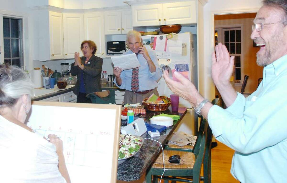 In his Lake avenue kitchen, Bill Grad, center, calls out the returns to the applause of his wife, Laura, and friend Winthrop Adkins, right, as Cynthia Keating writes the number on the board for the Democratic Primary for the Tax Collector position Tuesday evening, Sept. 15, 2009. He won the race against Rick Novakowski.