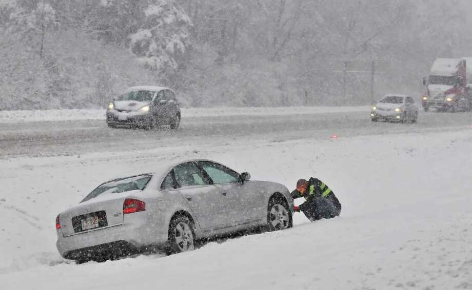 A tow truck driver prepares a car for a winch out on I87 between exits 7 and 8 Friday morning Feb. 25, 2011.  (John Carl D'Annibale / Times Union) Photo: John Carl D'Annibale / 00012200A