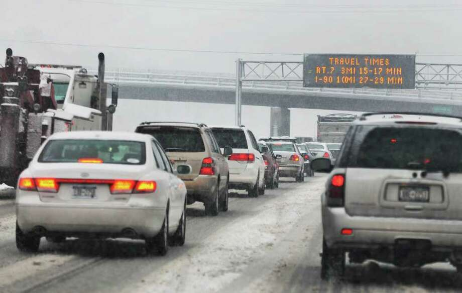 An optimistic road sign and traffic bogged down  in the southbound lanes of the Northway by a snowstorm Friday morning Feb. 25, 2011.  (John Carl D'Annibale / Times Union) Photo: John Carl D'Annibale / 00012200A