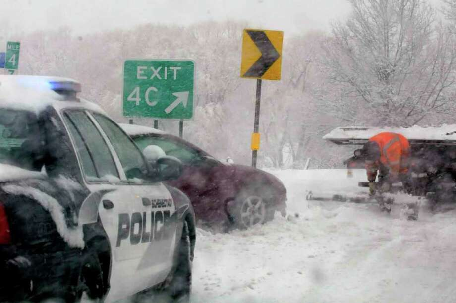 A motorist is assisted after sliding off the road on  890 in Schenectady Friday Feb. 25, 2011. ( Michael P. Farrell/Times Union ) Photo: Michael P. Farrell