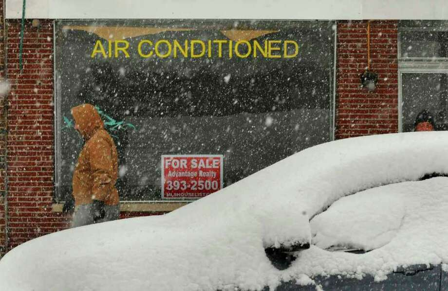 "A sign on a building for rent reads ""air conditioned"" as mid-morning snow falls on State Street in Schenectady Friday Feb. 25, 2011. ( Michael P. Farrell/Times Union ) Photo: Michael P. Farrell"