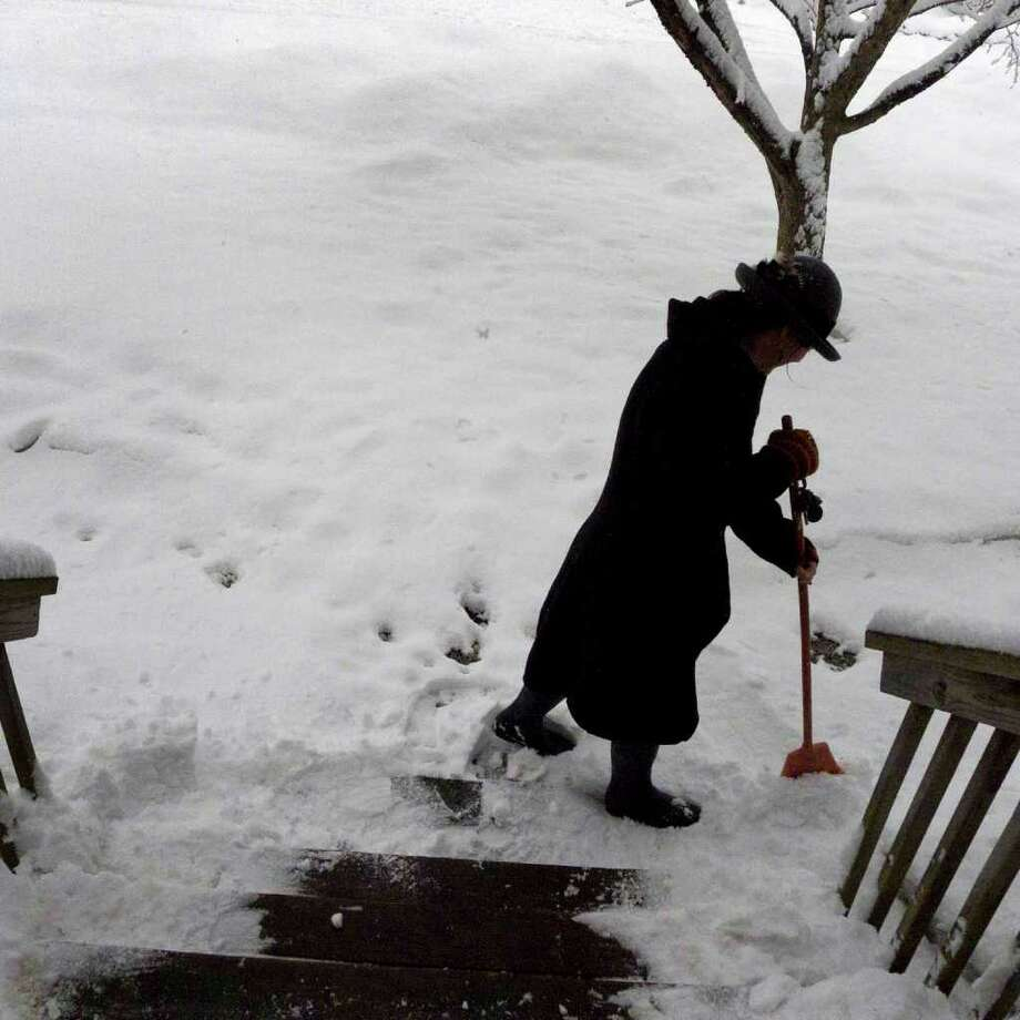 Lisa Reddy sweeps snow from her steps in Delmar on Friday Feb. 25, 2011. ( Michael P. Farrell/Times Union ) Photo: Michael P. Farrell / 00012200A