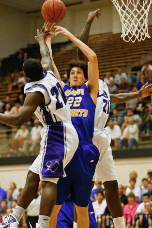 Alamo Heights Jeffery Rodewald (center) battles Austin LBJ's Deandre Byrd (left) and David Weathers for a rebounds during the first quater of their second round playoff game at Littleton Gym on Feb. 24, 2011.  Alamo Height won the game 48-45 to advance to the next round.  Photo by Marvin Pfeiffer Photo: Marvin Pfeiffer/Prime Time Newspapers