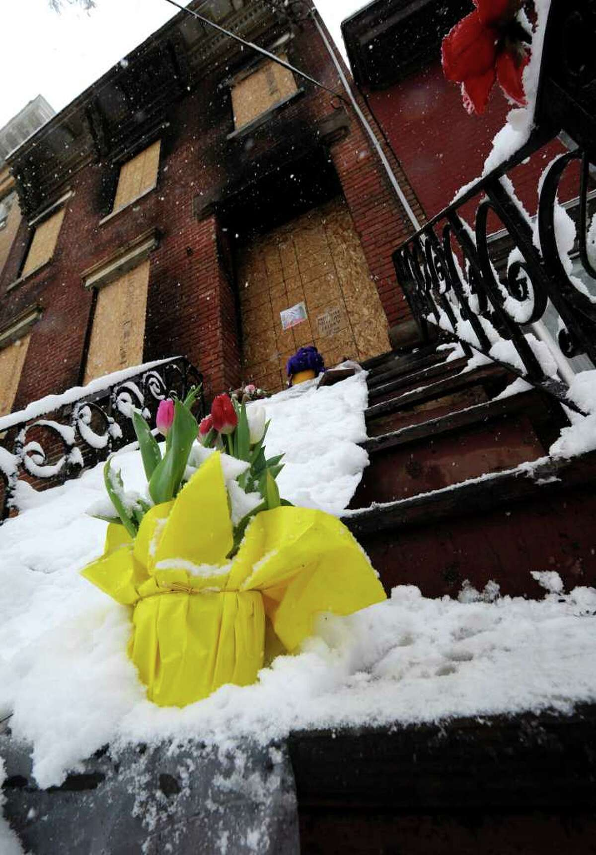 Flowers sit on the bottom step of the house where Trina McDowell perished in a fire Monday at 69 Grand St. in Albany.(Skip Dickstein / Times Union)