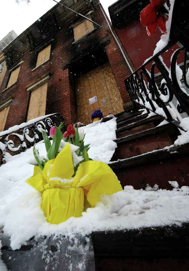 Flowers sit on the bottom step of the house where Trina McDowell perished in a fire Monday at 69 Grand St. in Albany.(Skip Dickstein / Times Union) Photo: Skip Dickstein