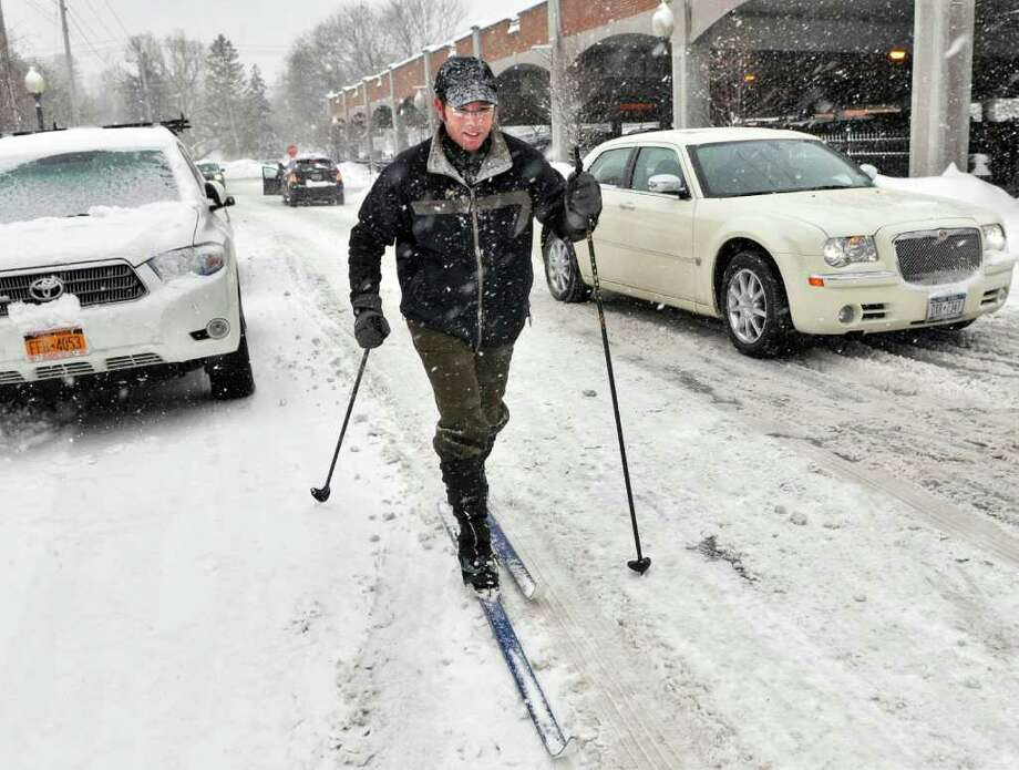 Architect Jeff Olsen skis through downtown Sartoga Springs on his way to a business meeting Friday afternoon Feb. 25, 2011.  (John Carl D'Annibale / Times Union) Photo: John Carl D'Annibale / 00012200A