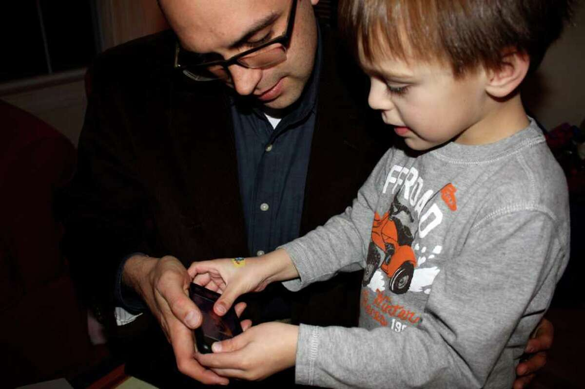 Dan Tedesco of Shelton helps his son Evan, 6, who has been diagnosed with autism, using an app he and his wife Carey designed for the iPhone and iPad.