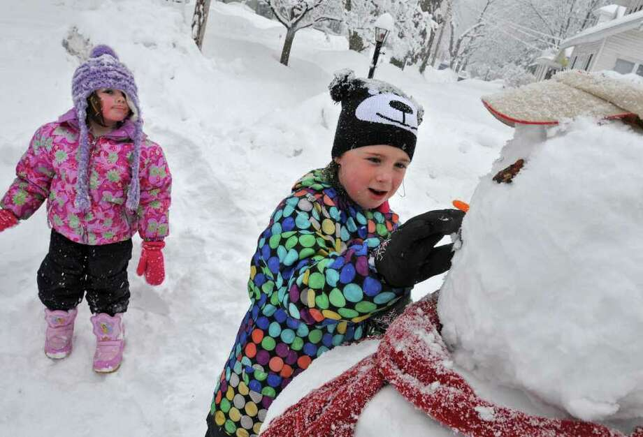 Loretta Ader, age 4, watches her older sister Bridget Neiler-Auger, age 7, put a mouth on the snowman they built at their grandmother's home in Guilderland, NY, on Friday, February 25, 2011.  (Lori Van Buren / Times Union) Photo: Lori Van Buren