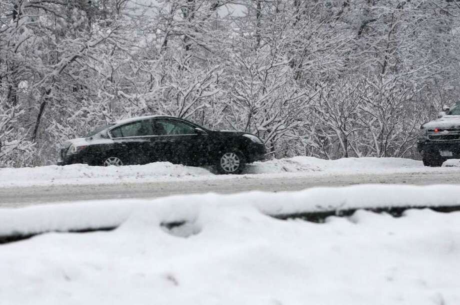 A car is stuck after sliding off I-87 northbound near exit 1 in Albany, NY, on Friday, February 25, 2011.  (Lori Van Buren / Times Union) Photo: Lori Van Buren
