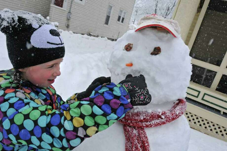 Bridget Neiler-Auger, age 7, tries to put a mouth on the snowman she and her sister built at their grandmother's home in Guilderland, NY on Friday, February 25, 2011.  (Lori Van Buren / Times Union) Photo: Lori Van Buren