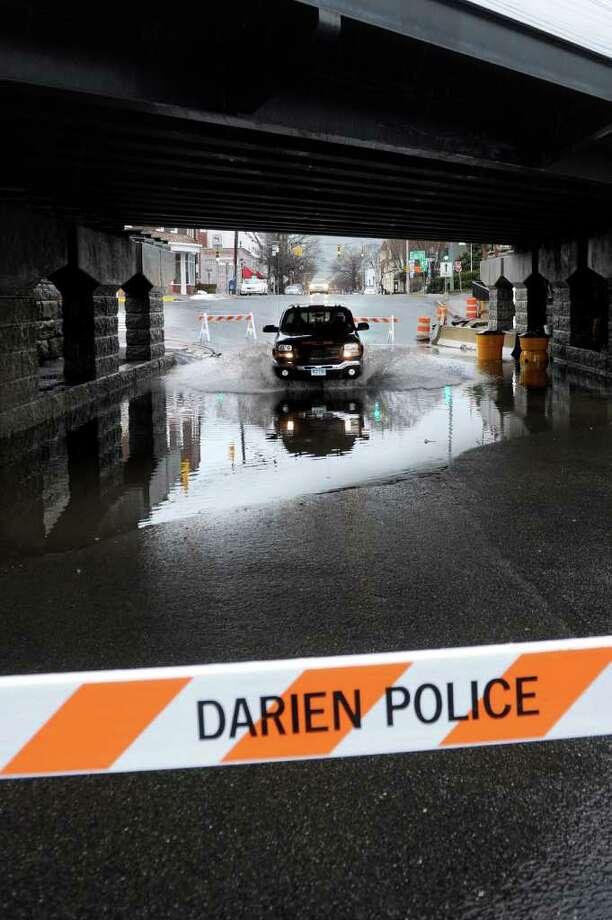 Cars drive through the closed road at the flooded intersection of Mechanic Street and Old Post Road in Darien on Friday, February 25, 2011. Photo: Lindsay Niegelberg / Connecticut Post