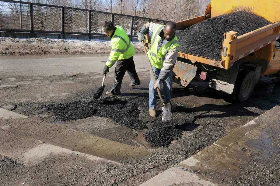 Dale Johnson, left, of New Fairfield and Leon Breece of Danbury, employees of the Danbury highway department fill potholes on Westville Avenue Ext. in Danbury Wednesday, Feb. 23, 2011. Photo: Carol Kaliff / The News-Times