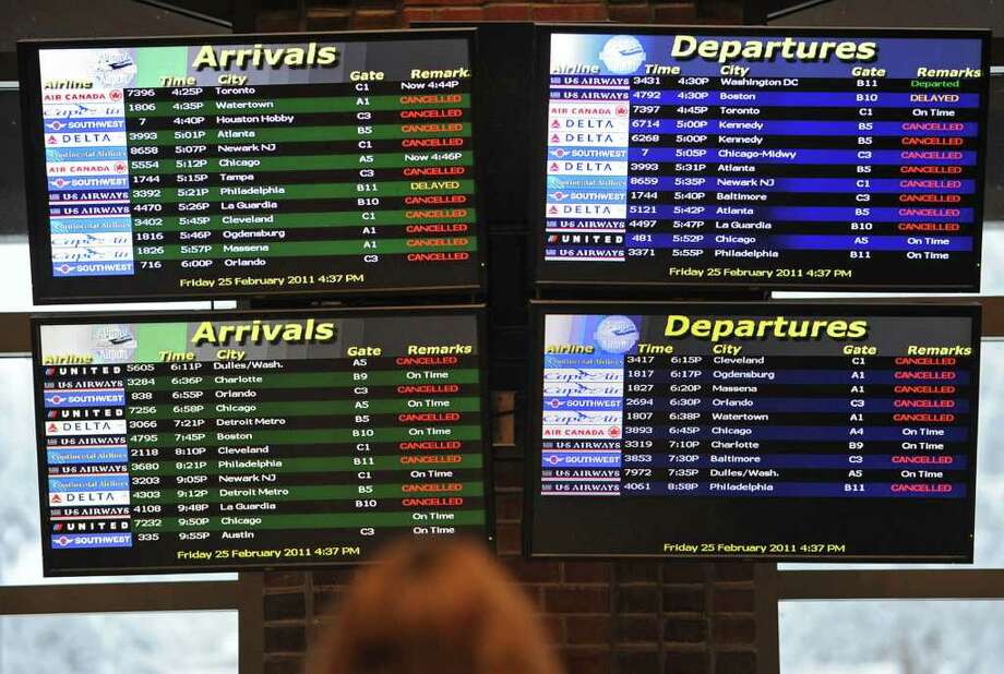 A passenger checks the arrival and departure screens at the Albany International Airport in Colonie, NY on Friday, February 25, 2011. Many flights were cancelled due to a snow storm. (Lori Van Buren / Times Union) Photo: Lori Van Buren