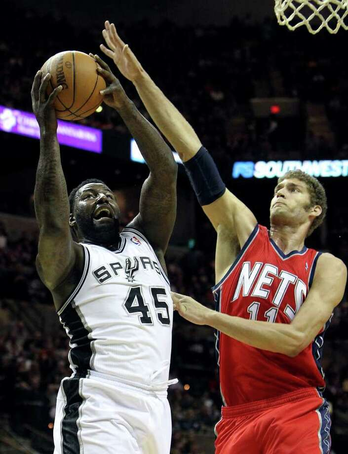 Spurs' DeJuan Blair (45) goes up for a basket against New Jersey Nets' Brook Lopez (11) in the first half at the AT&T Center on Friday, Feb. 25, 2011. Blair scored 13 points in the first quarter. Kin Man Hui/kmhui@express-news.net Photo: KIN MAN HUI, SAN ANTONIO EXPRESS-NEWS / kmhui@express-news.net
