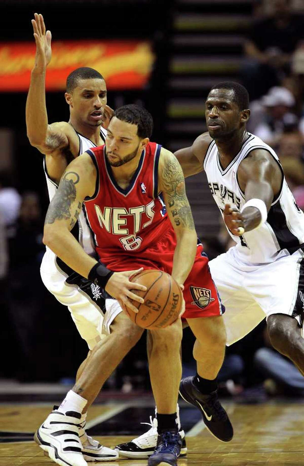 Spurs' George Hill (left) and Antonio McDyess (right) defend against New Jersey Nets' Deron Williams (08) in the first half at the AT&T Center on Friday, Feb. 25, 2011. Kin Man Hui/kmhui@express-news.net