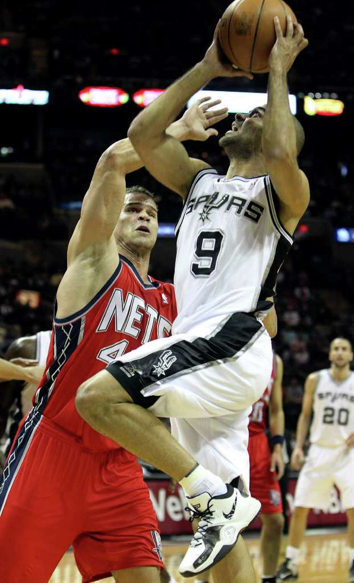 Spurs' Tony Parker (09) drives to the basket against New Jersey Nets' Kris Humphries (43) in the first half at the AT&T Center on Friday, Feb. 25, 2011. Kin Man Hui/kmhui@express-news.net