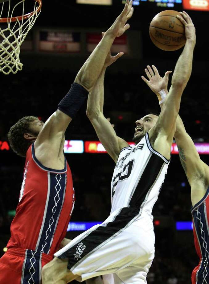 Spurs' Manu Ginobili (20) goes up for a shot against New Jersey Nets' Brook Lopez (11) in the first half at the AT&T Center on Friday, Feb. 25, 2011. Kin Man Hui/kmhui@express-news.net Photo: KIN MAN HUI, SAN ANTONIO EXPRESS-NEWS / kmhui@express-news.net