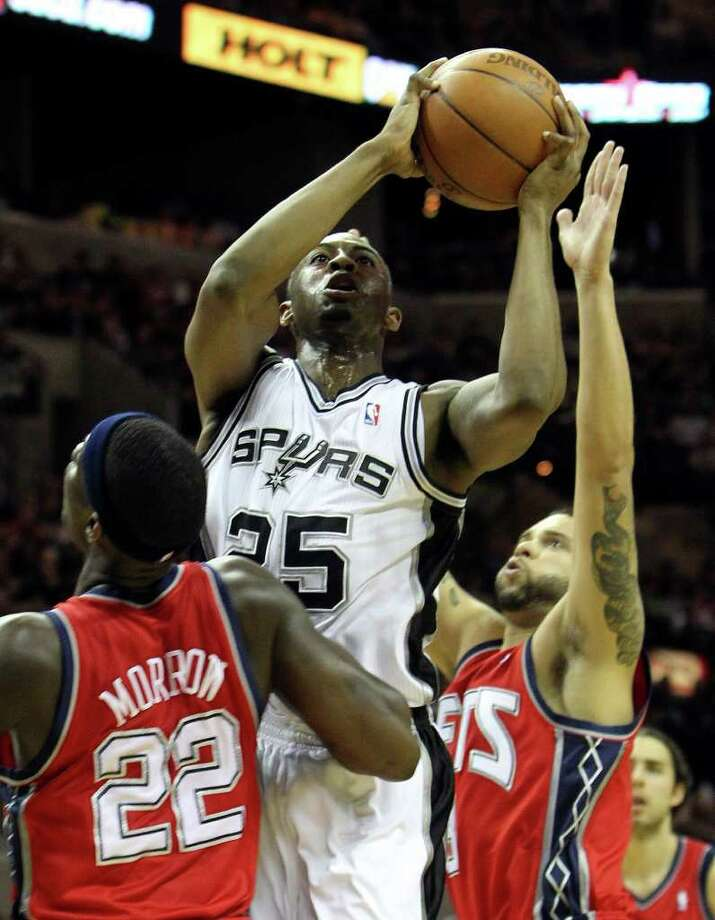 Spurs' James Anderson (25) shoots against New Jersey Nets' Anthony Morrow (22) and Deron Williams (right) in the first half at the AT&T Center on Friday, Feb. 25, 2011. Kin Man Hui/kmhui@express-news.net Photo: KIN MAN HUI, SAN ANTONIO EXPRESS-NEWS / kmhui@express-news.net