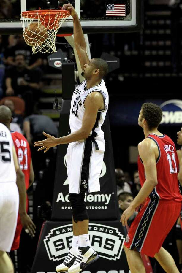 Spurs' Tim Duncan (21) dunks against New Jersey Nets' Brook Lopez (11) in the second half at the AT&T Center on Friday, Feb. 25, 2011. Spurs won, 106-96. Kin Man Hui/kmhui@express-news.net Photo: KIN MAN HUI, SAN ANTONIO EXPRESS-NEWS / kmhui@express-news.net