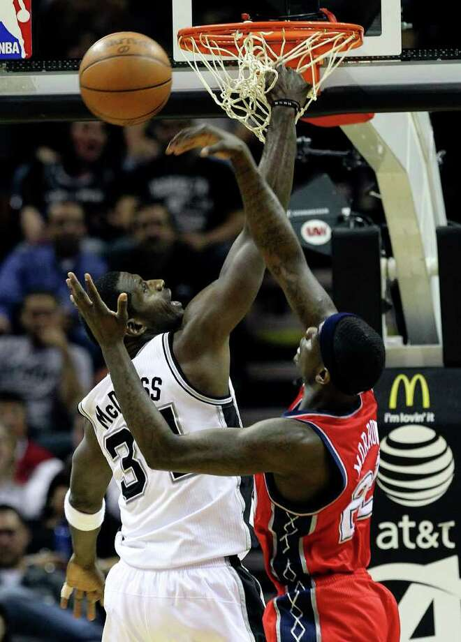 Spurs' Antonio McDyess (34) gets his hand caught in the net while defending against New Jersey Nets' Anthony Morrow (22) in the second half at the AT&T Center on Friday, Feb. 25, 2011. Spurs won, 106-96. Kin Man Hui/kmhui@express-news.net Photo: KIN MAN HUI, SAN ANTONIO EXPRESS-NEWS / kmhui@express-news.net