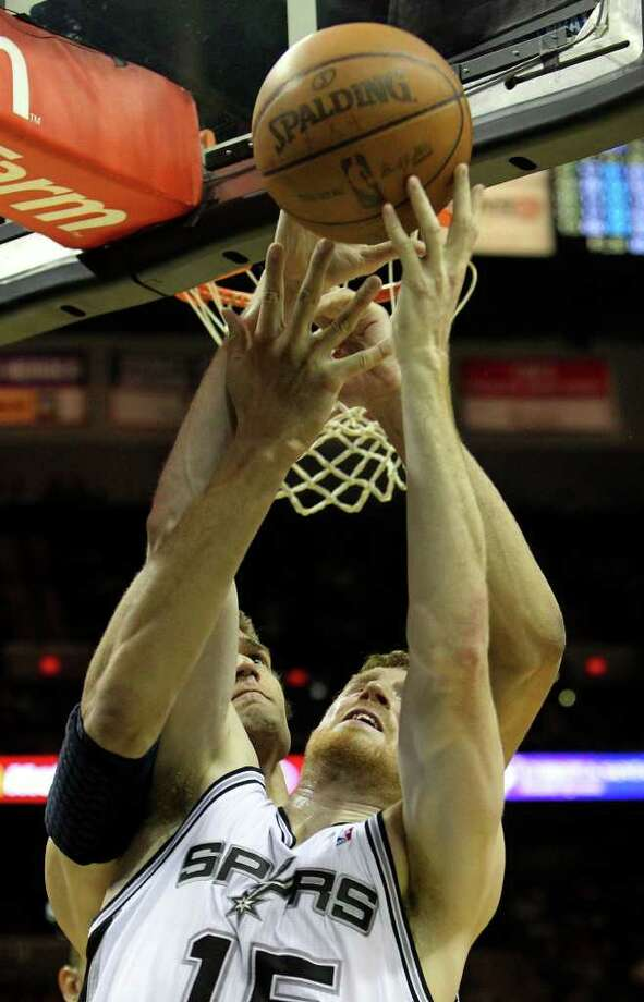 Spurs' Matt Bonner (front) and New Jersey Nets' Brook Lopez get tangled while reaching for a rebound in the second half at the AT&T Center on Friday, Feb. 25, 2011. Spurs defeated the Nets, 106-96. Kin Man Hui/kmhui@express-news.net Photo: KIN MAN HUI, SAN ANTONIO EXPRESS-NEWS / kmhui@express-news.net