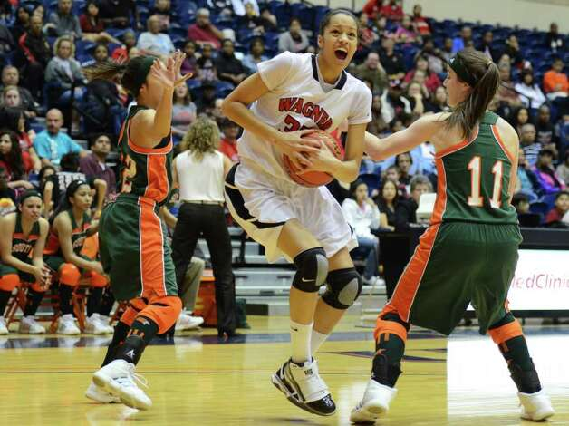 Wagner senior Arielle Roberson (33) drives the ball between two Harlingen defenders during the Region IV-5A girls semifinal basketball game between the Wagner T-Birds and the Harlingen South in the UTSA Convocation Center in San Antonio, Texas on February 25, 2011  John Albright / Special to the Express-News. Photo: JOHN ALBRIGHT, San Antonio Express-News / San Antonio Express-News