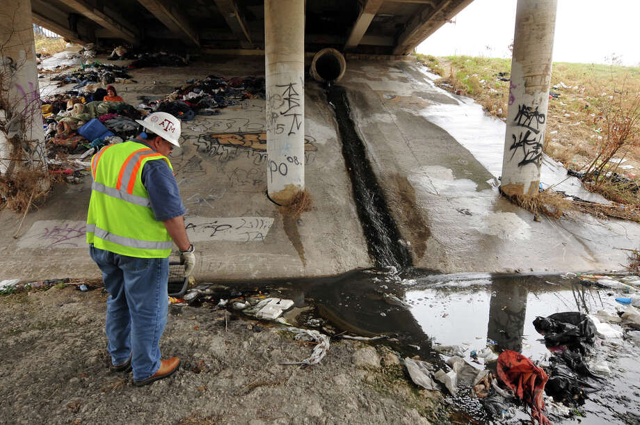 Gerald Johnson, an environmental protection specialist with SAWS, eyes the flow from a storm drain under the Brazos Street Bridge. Photo: Robin Jerstad/Special To The Express-News / Copyright 2011 by Robin Jerstad, 210-254-6552