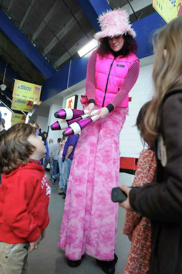 "From left, Wyatt Aslanian, age 5, with sisters Zabelle, age 7 and Grace, age 10, of Westchecter, watch Colleen Mahar, aka ""Sparkles The Tall Juggler,"" during the state high school wrestling quarerfinals at the Times Union Center in Albany, NY on Friday, February 25, 2011.  (Lori Van Buren / Times Union) Photo: Lori Van Buren"