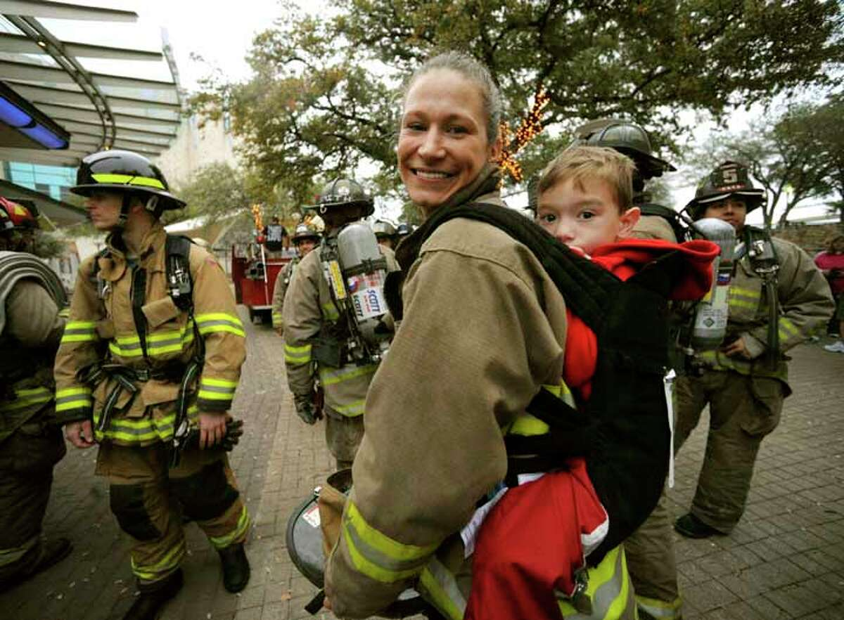 Firefighter Dawn Solinski prepares to climb the Tower of the Americas while carrying Wesley Stanfield, a four-year-old child who is battling cystic fibrosis, during the Cystic Fibrosis Foundation