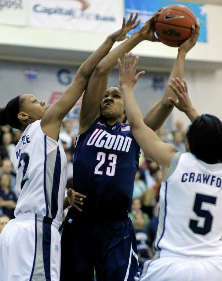 Connecticut forward Maya Moore, 23, center, is tied-up by Georgetown forwards Tia Magee, 2, left, and Adria Crawford during the first period of their Big East game in Washington, Saturday, Feb. 26, 2011. (AP Photo/Cliff Owen) Photo: AP