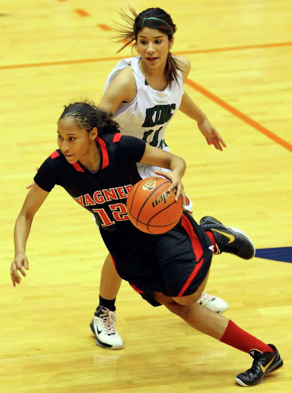 FOR SPORTS - Wagner's Aundrea Davis drives around Corpus Christi King's Melanie Cavazos during first half action of the Region IV-5A final Saturday Feb. 26, 2011 at the UTSA Convocation Center. (PHOTO BY EDWARD A. ORNELAS/eaornelas@express-news.net)