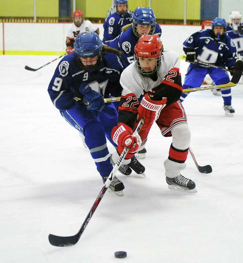 New Canaan High School's Olivia Hompe reaches for the puck with pressure from Darien High School's Sara Shaker in the girls hockey FCIAC championship game at Terry Conners Rink in Stamford, Conn. on Saturday February 26, 2011. New Canaan won 7-1.