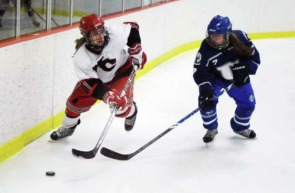 New Canaan High School's Molly Burwick races for the puck against Darien High School's Lily Christensen in the girls hockey FCIAC championship game at Terry Conners Rink in Stamford, Conn. on Saturday February 26, 2011. New Canaan won 7-1.