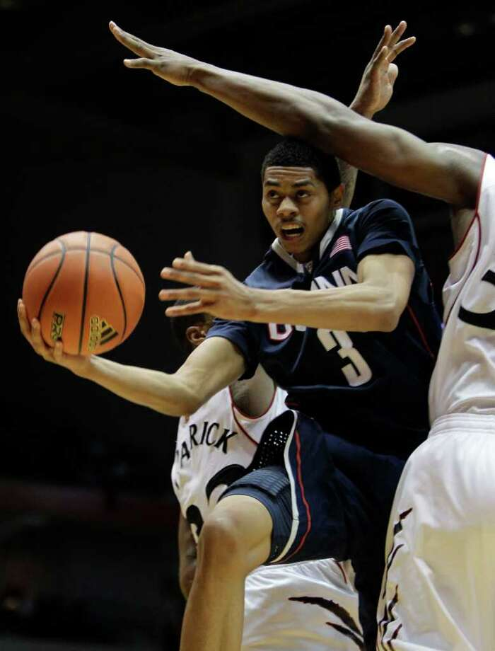 Connecticut guard Jeremy Lamb (3) drives between Cincinnati guard Sean Kilpatrick, left, and forward Yancy Gates in the second half of an NCAA college basketball game, Sunday, Feb. 27, 2011, in Cincinnati. Lamb led Connecticut to a 67-59 win with 17 points. (AP Photo/Al Behrman) Photo: Al Behrman, AP / Associated Press