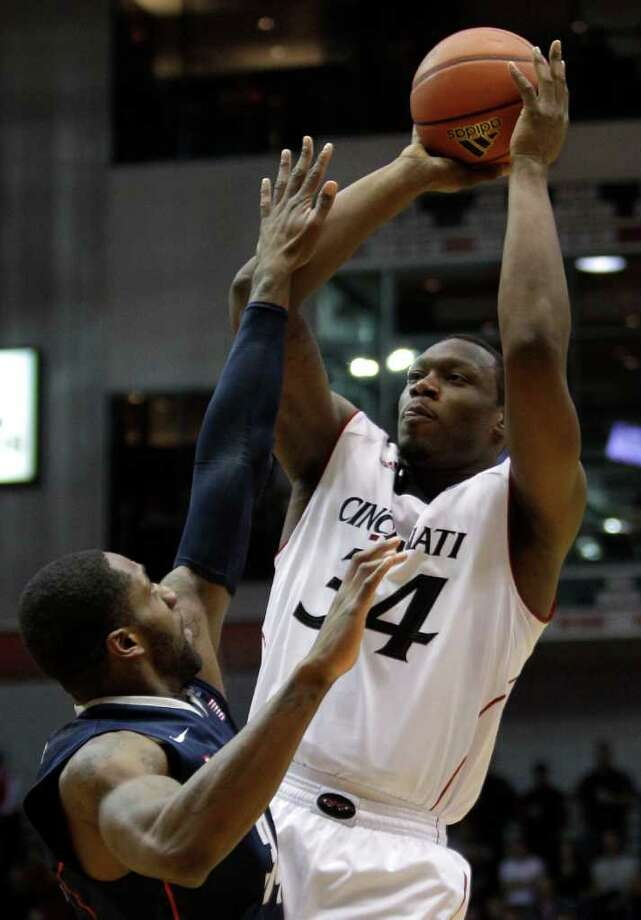 Cincinnati forward Yancy Gates (34) shoots over Connecticut forward/center Alex Oriakhi in the first half of an NCAA college basketball game, Sunday, Feb. 27, 2011, in Cincinnati. (AP Photo/Al Behrman) Photo: Al Behrman, ASSOCIATED PRESS / ASSOCIATED PRESS
