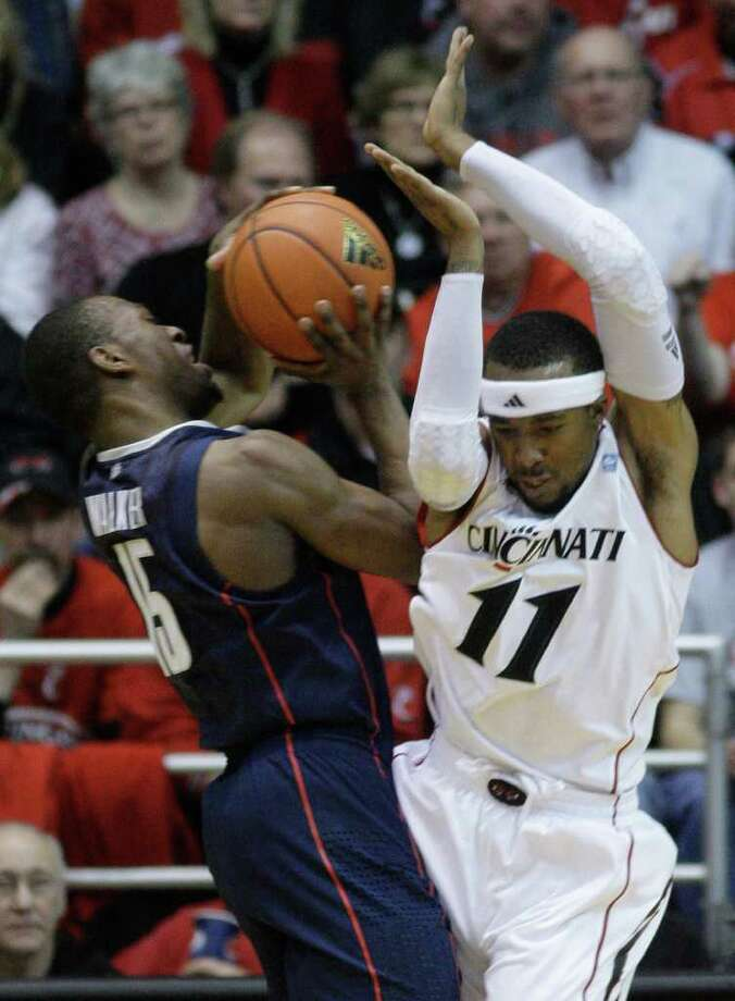 Connecticut guard Kemba Walker (15) is fouled by Cincinnati guard Larry Davis (11) in the first half of an NCAA college basketball game, Sunday, Feb. 27, 2011, in Cincinnati. (AP Photo/Al Behrman) Photo: Al Behrman, ASSOCIATED PRESS / ASSOCIATED PRESS