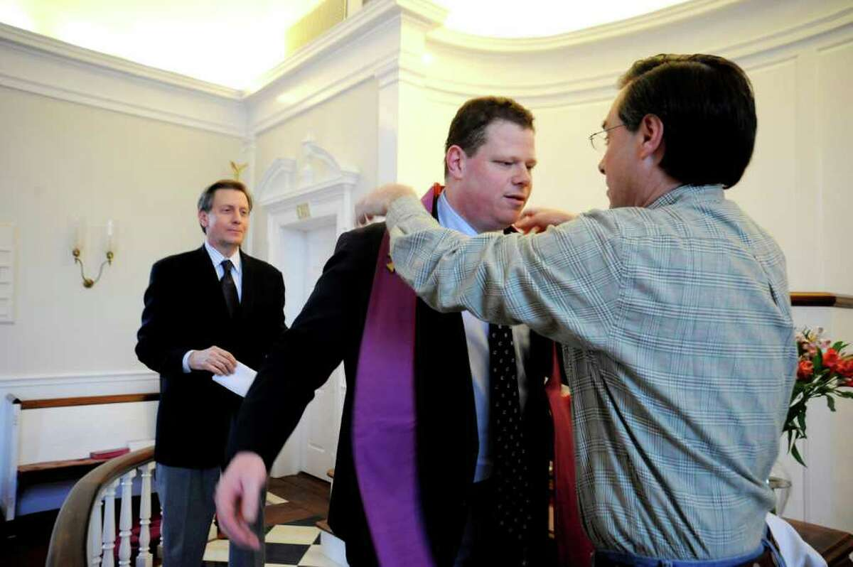 Sean Witty, new associate pastor, center, receives a stole from Chis Cole, while Steve Pisarkiewicz, lay leader, left, watches, at the installation at the First Church of Round Hill, on Sunday, Feb. 27, 2011.